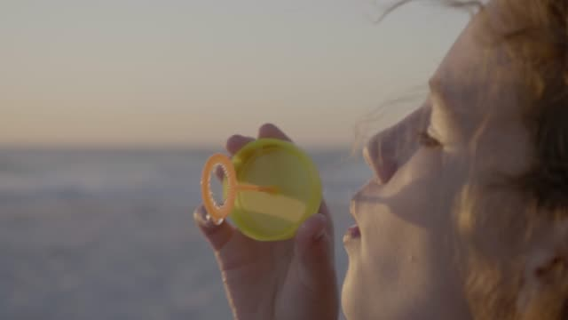 vídeos de stock, filmes e b-roll de close-up of girl blowing soap bubble at beach - espuma