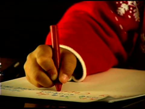 vídeos de stock e filmes b-roll de close-up of girl writing letter to santa for christmas - pai natal