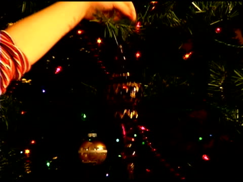 vídeos de stock, filmes e b-roll de close-up of girl's hand putting ornament on christmas tree - decoração de natal