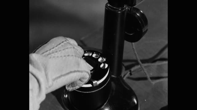 1952 close-up of gloved hand dialing number on telephone - linea telefonica video stock e b–roll