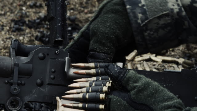 Close-up of gloved hands loading a chain of rounds.
