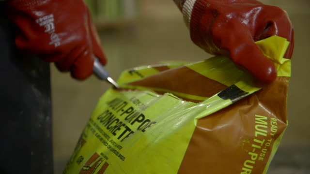 Close-up of gloved hands opening a bag of concrete mix with a Stanley knife, UK.