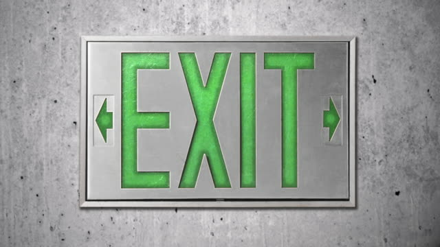 close-up of green exit sign on concrete wall - blinking arrow stock videos & royalty-free footage