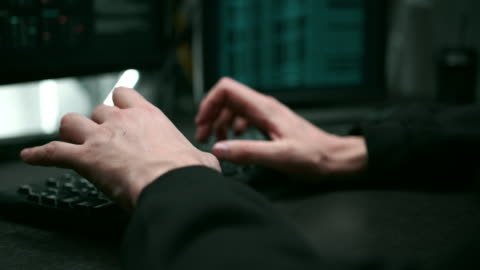vidéos et rushes de plan rapproché des mains du pirate dactylographiant le code du programme sur l'ordinateur portable - risque