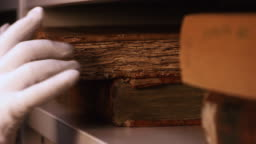 Close-up of hand in white cotton glove taking very old book from the bookshelf in museum or private library. Stock footage. Exploring of the ancient yellowed books