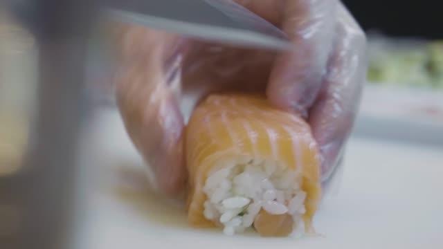vídeos de stock, filmes e b-roll de close-up de mão preparando sushi arregaçando - comida salgada