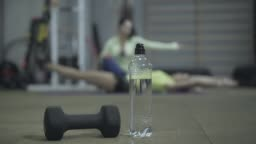 Close-up of hand weights and water bottle standing on the floor in gym with blurred slim woman training at the background. Personal trainer controlling TRX exercise. Workout, pumping press, coaching.