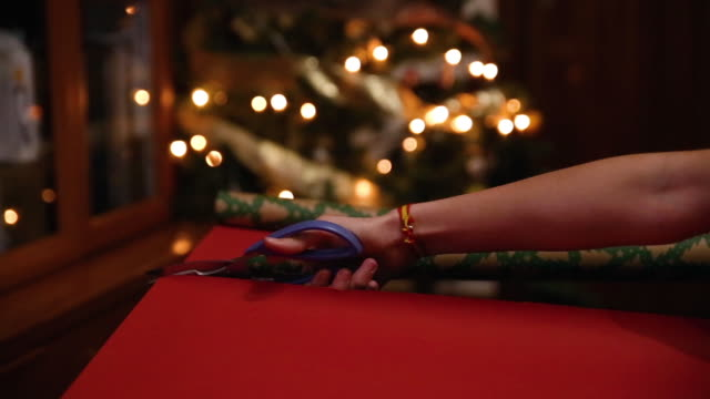 close-up of hands cutting a wrapping paper with scissors in the living room at home next to the christmas tree - christmas wrapping paper stock videos & royalty-free footage
