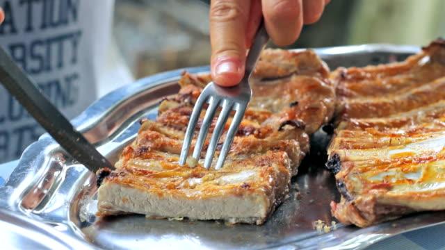 vídeos y material grabado en eventos de stock de close-up of hands cutting delicious pork ribs - modales de mesa
