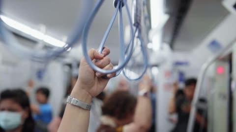 stockvideo's en b-roll-footage met close-up van handen houden leuning of grip riemen in metro trein, slow motion - veiligheidshek