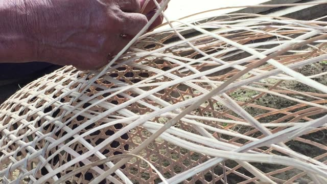 Close-up of hands of middle-aged Kichwa Indian male weaving a natural plant-based basket in the autonomous indigenous region of Sarayaku in the Ecuadorian Amazon