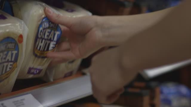 vídeos de stock e filmes b-roll de close-up of hands picking up and putting back a loaf of white bread at a uk supermarket. - vendas