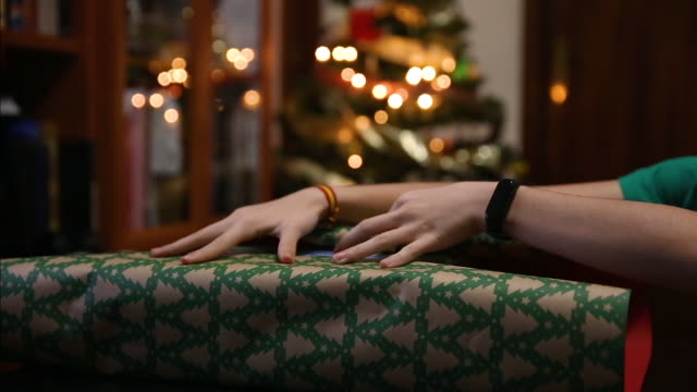 close-up of hands placing a wrapping paper on a gift box in the living room at home next to the christmas tree - christmas wrapping paper stock videos & royalty-free footage