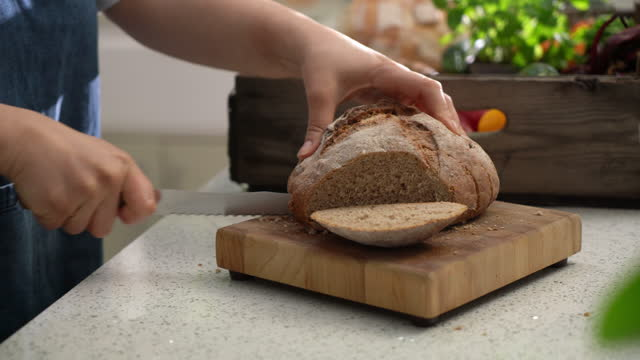 closeup of hands slicing loaf of bread in kitchen - loaf of bread stock videos & royalty-free footage