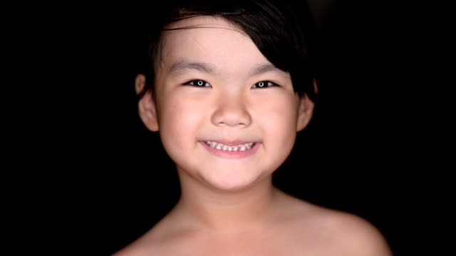 Closeup of happy little girl isolated on black background