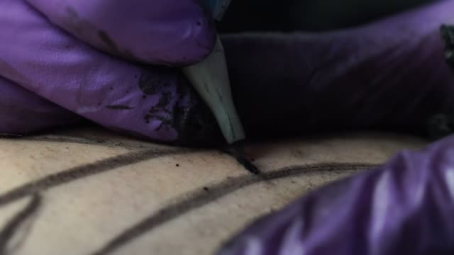 close-up of having permanent tattoo in tattoo studio - hsyncoban stock videos and b-roll footage