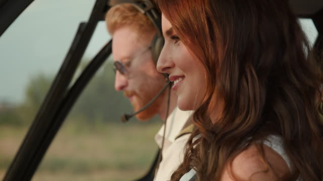 close-up of helicopter pilot and female passenger in cockpit - helicopter stock videos & royalty-free footage