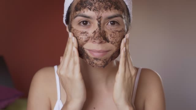 close-up of hispanic young woman applying coffee scrub mask on her face after taking a bath - scrubs stock videos & royalty-free footage