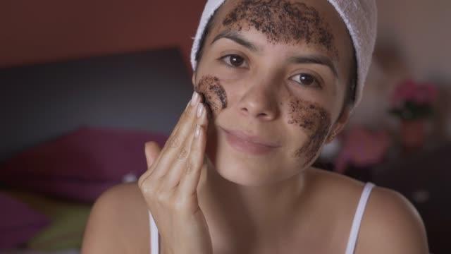 お風呂の後、彼女の顔にコーヒースクラブマスクを適用するヒスパニック系の若い女性のクローズアップ - ゴシゴシ洗う点の映像素材/bロール