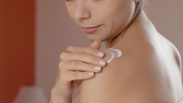 入浴後の体に保湿クリームを塗布するヒスパニック系の若い女性のクローズアップ - クリーム点の映像素材/bロール