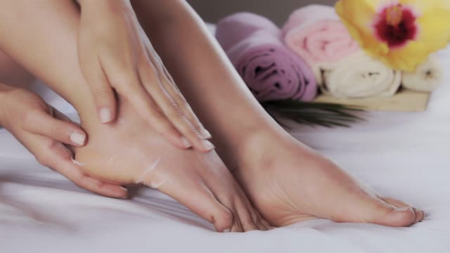 close-up of hispanic young woman applying moisturizing cream on her feet after taking a bath - moisturiser stock videos & royalty-free footage