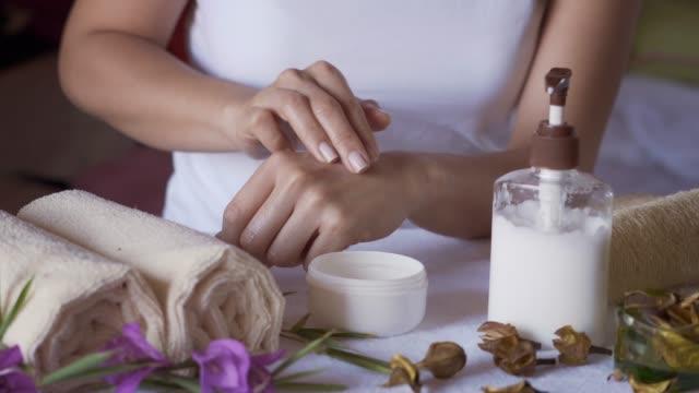 彼女の手に保湿クリームを適用するヒスパニック系の若い女性のクローズアップ - タオルにくるまる点の映像素材/bロール