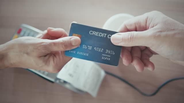vidéos et rushes de plan rapproché de la main humaine donnant la carte de crédit au vendeur, mouvement lent - boutique
