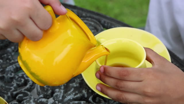 close-up of human hand pouring tea into a cup from tea pot - tea pot stock videos and b-roll footage