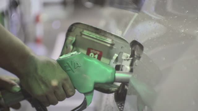 close-up of human hand refueling car at gas station pump,slow motion - consumerism stock videos & royalty-free footage