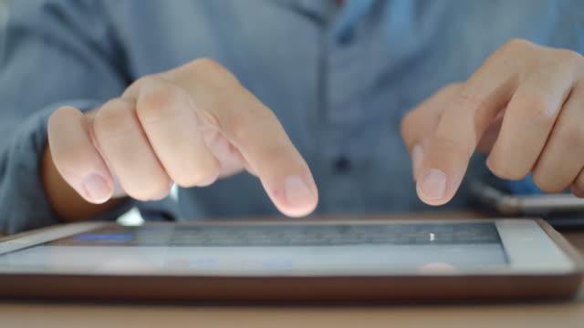 vídeos de stock, filmes e b-roll de close-up de mãos humanas digitando em tablet digital - portability