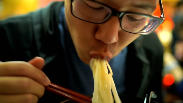 vídeos de stock e filmes b-roll de close-up of hungry man eating noodle ramen - comida chinesa