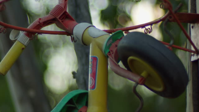 close-up of kid tricycle hanging from a basketball hoop in theme park - tricycle stock videos & royalty-free footage
