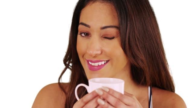 vídeos de stock e filmes b-roll de closeup of latina female holding coffee mug and winking at camera in studio - cabelo natural