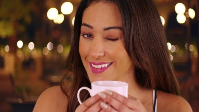 vídeos de stock e filmes b-roll de closeup of latina female holding coffee mug outdoors at night, winking at camera - cabelo natural