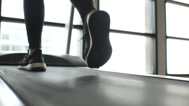 close-up of leg running on treadmill, woman exercising in the gym - muscular build stock videos & royalty-free footage