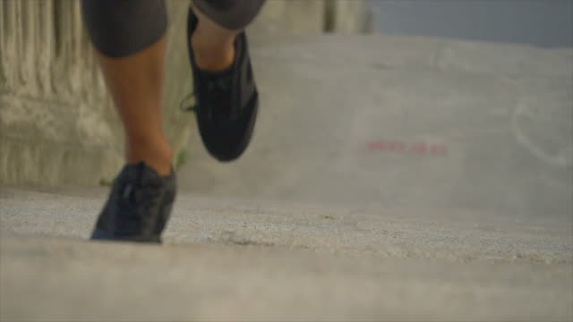 closeup of legs on a woman running on stairs in a city for a workout. - slow motion - stufen stock-videos und b-roll-filmmaterial