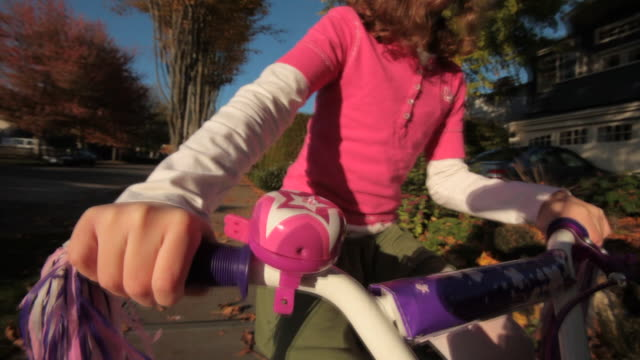 closeup of little girl in pink as she rides her bicycle along a sidewalk. - bell stock videos and b-roll footage