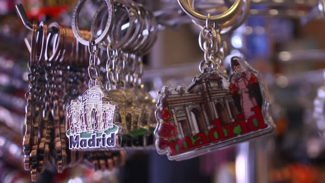 close-up of madrid key rings on display in shop in slow motion, madrid, spain - souvenir stock videos and b-roll footage