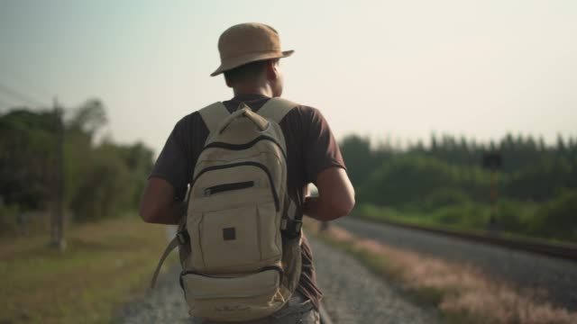 stockvideo's en b-roll-footage met close-up van de mannelijke backpacker lopen op railroad - rear view