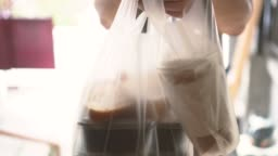 Close-up of male food delivery man on service job giving foods of bubble tea, coffee, lunch box at home