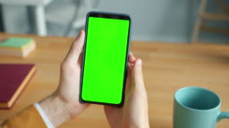 Close-up of male hands holding chroma key green screen smartphone in office