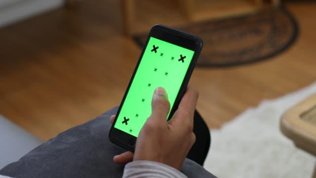 Nahaufnahme der männlichen Hand hält Smartphone mit der green-screen