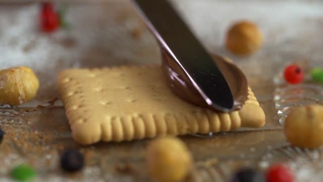 vídeos y material grabado en eventos de stock de primer plano de manos hombres separarse mantequilla en las galletas en la cocina, lenta - untar