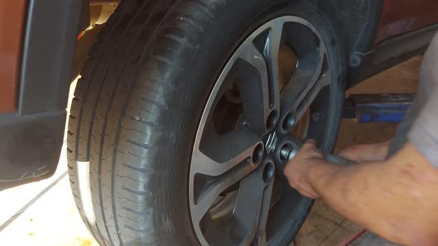 男性技術者のメカニックのクローズアップは、車のホイールを変更しています - 交代点の映像素材/bロール