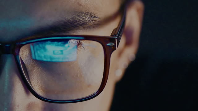 Closeup Of Man Eye In Glasses Watching On Computer