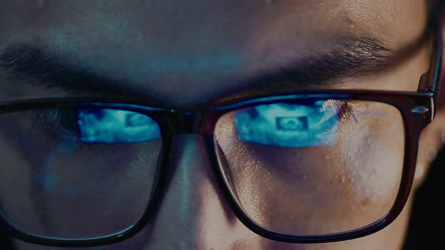 closeup of man eye in glasses watching on computer - concentration stock videos & royalty-free footage