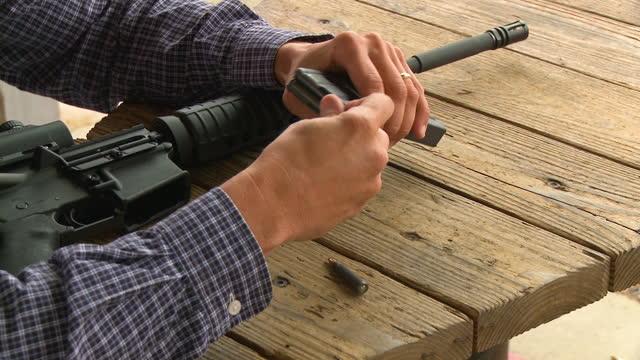 close-up of man filling ammunition magazine of machine gun - machine gun stock videos & royalty-free footage