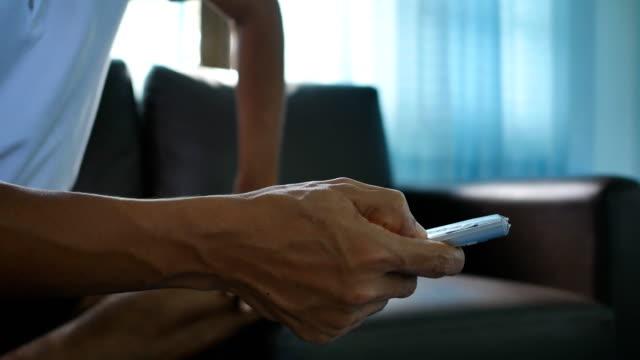 nahaufnahme der hand des mannes mit tv-fernbedienung - fade in video transition stock-videos und b-roll-filmmaterial