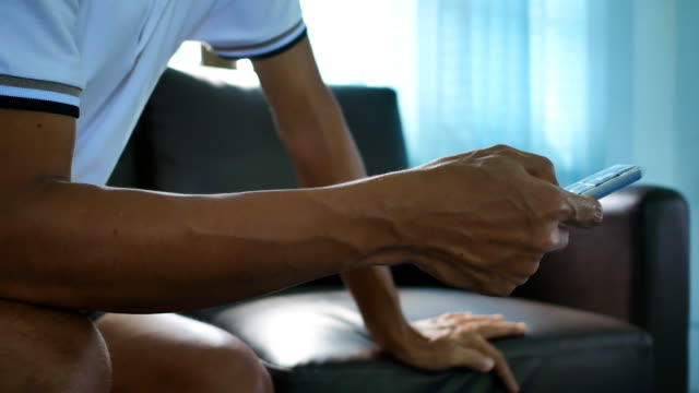 Nahaufnahme der Hand des Mannes mit TV-Fernbedienung