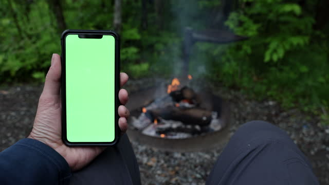 close-up of man hands reading on chroma key green screen mobile phone by the campfire - holding stock videos & royalty-free footage